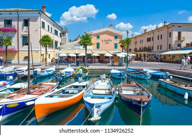 Bardolino, Italy - August 11, 2008: Garda lake, boats and tourists  in the old harbor