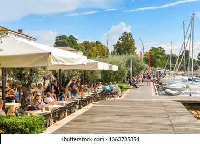 BARDOLINO, LAKE GARDA, ITALY - SEPTEMBER 2018: People sitting in a restaurant in Bardolino on the boardwalk on he edge of Lake Garda.