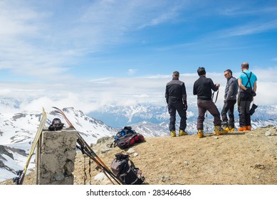 Bardonecchia, Italy - May 23, 2015: Group of four alpinists chatting in scenic high altitude background on the M. Sommeiller summit (3333 m) in the italian french Alps in a sunny day of springtime.