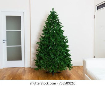 Bare artificial christmas tree in house with white furnishings and oak parquet flooring.