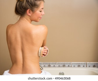 Bare back of young woman holding dry brush to her side