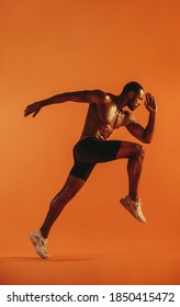Bare chested athlete running with big stride forward on orange background. African american sportsman sprinting.