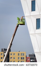 Bare chested construction worker wearing safety harness on an aerial access platform