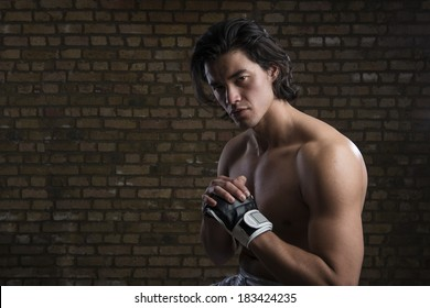 Bare chested young Malaysian boxer wearing fingerless boxing gloves