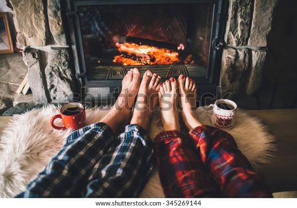Nur wenige Meter vom gemütlichen Kamin entfernt. Mann und Frau entspannen sich durch warmes Feuer mit einer Tasse heißen Getränks und wärmen sich die Füße auf. Nahaufnahme zu Füßen. Konzept der Winter- und Weihnachtsferien.