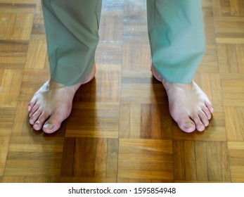 Bare feet / barefoot of adult male wearing long trousers against a wooden floor. To illustrate going barefoot