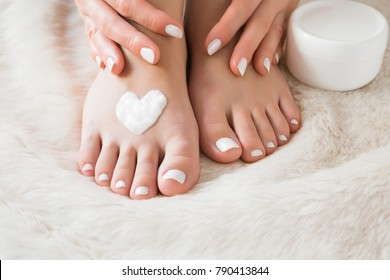 Bare feet. Beautiful groomed woman's feet with cream jar on the fluffy mat. Cares about clean and soft legs skin in winter time. Heart shape created from cream. Love a body. Healthcare concept.