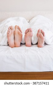 Bare feet of gay couple out from the blanket in bed