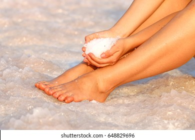 bare feet girls on the shore of the Dead Sea, and in the hands of sea salt