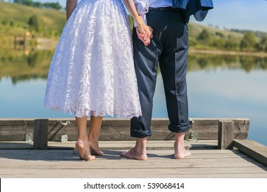 Bare feet of groom and bride standing close to each other near the lake