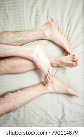 Bare feet and hairy legs of homosexual men during sleep