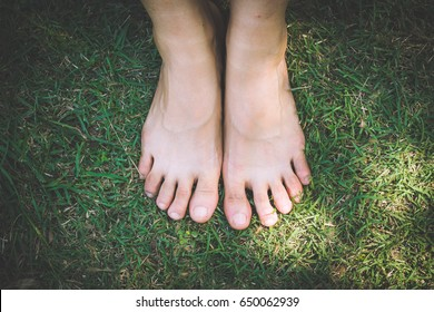 bare feet and hands with creative teens manicure and pedicure on the green grass lawn background,Foot over green grass