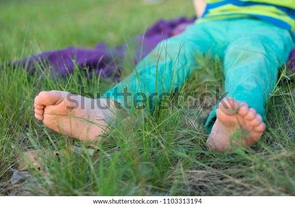 bare feet of a little boy on the grass