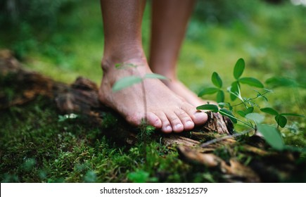 Bare feet of man standing barefoot outdoors in nature, grounding concept.