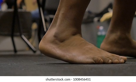 Bare feet on a mortar floor background. Bare feet of an athlete. The legs of the boxer in the locker room before the fight, he is very excited and finds no place