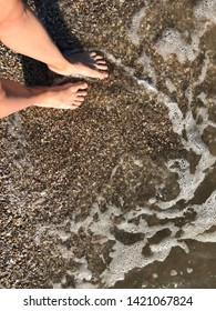 Bare feet on the sea sand near the water