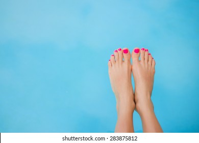 Bare feet over blue swimming pool water