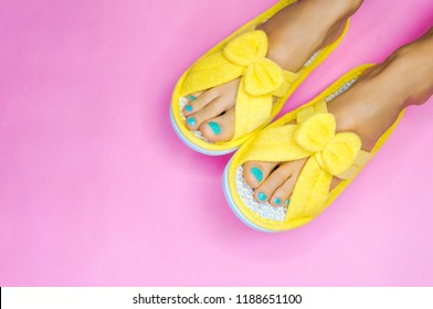 Bare feet with pedicure and wearing yellow funny slippers  over pink background