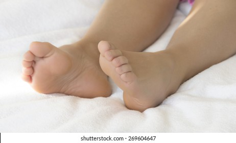bare feet of a woman in bed