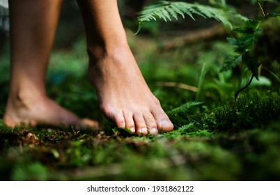 Bare feet of woman standing barefoot outdoors in nature, grounding concept.