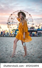 Bare feet woman walking on the beach sand in hand at sunset time near amusement park rides.