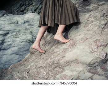 The bare feet of a young woman as she is climbing up a rock surface