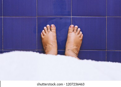 Bare female feet on blue vintage plate tile, top view. The concept of women's health skin and nails care. Healthy foot, flat feet, pes planus,fallen arches, copy space