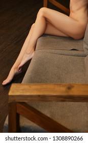 Bare female legs on sofa