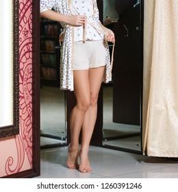 Bare female legs standing on the floor near dressing room in pajama