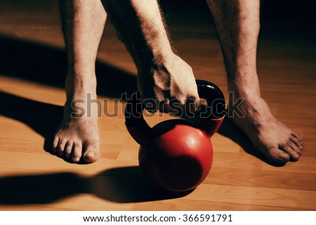 Bare Foot Man Reaching Out For A Weight Preparing For A Workout Session