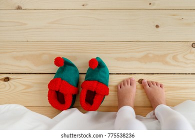 Bare foot of small kid standing on wooden floor, awaking in morning, going to wear elf s shoes. Unrecognizable child on wooden surface. Christmas time. Holidays concept.