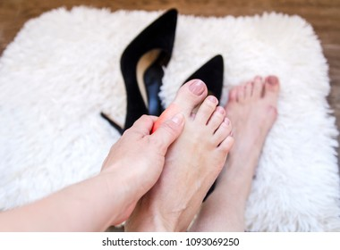 Bare foot of woman with painful red bunion and injury foot after walk in high heels.Close up on female feet and hand massage fatique spot.