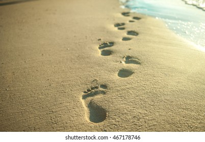 bare footsteps on the sand on a beach. the sand is white and the steps can be of man or women. Footsteps on the coral sandy beach