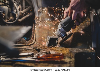 Bare hands of a man using an angle grinder to cut off the excess rusty metal from a car body in attempt to restore it and weld in a new piece. Sparks flying around, tools and grinding plates visible