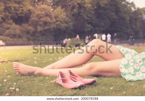 The bare legs of a young woman as she is relaxing on the grass in a park