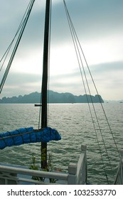 The bare mast and ropes of a boat frame a view over the islands of Halong Bay in Vietnam. It is late afternoon, and the sky is overcast. The water is grey. Some boats are in the distance.