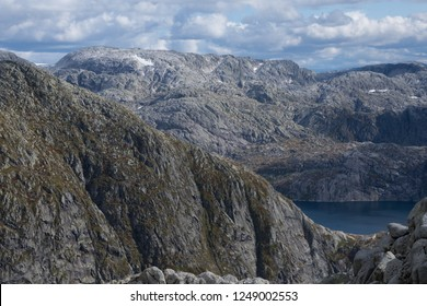 Bare mountain ridges near the glacier, lake with glacial water in the nearest valley. Norway.