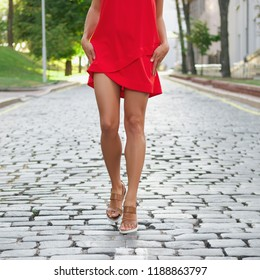 Bare tan and muscular legs on cobblestone pavement