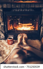 Bare woman feet by the cozy fireplace. Woman relaxes by warm fire with a cup of hot drink and warming up her feet. Close up on feet. Winter and Christmas holidays concept.