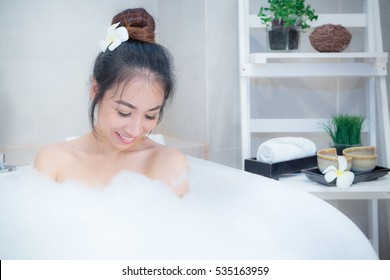 Bare woman sitting in Jacuzzi tub with cup of tea in thailand