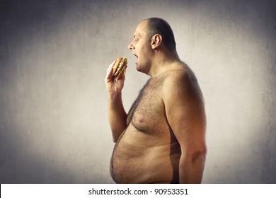 Bare-chested fat man eating a hamburger