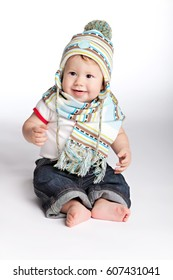 Barefoot baby boy sitting in a striped knitted cap and scarf of muffled tones on a white background