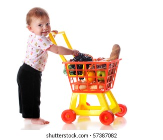 "A barefoot baby girl ""shopping"" for groceries with a toy shopping cart.  Isolated on white."