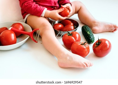 Un bebé descalzo juega a morder tomates rojos y a manchar su jugo.