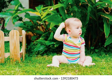 Barefoot baby sitting on the grass scratching his head thoughtfully.
