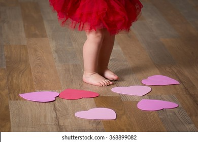 Barefoot baby standing on the floor with scattered  paper hearts.