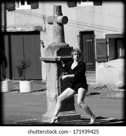 Barefoot blond dancer at the foot of a wayside cross in  Mirande, a french village.