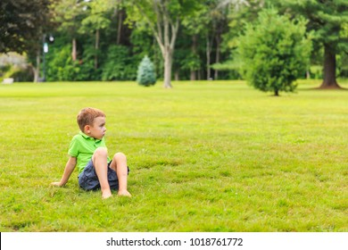 barefoot boy sitting on the lawn. cute kid in the park. Looking away. copy space for your text