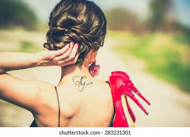 Brune nuptiale en plein air, talons rouges dans les mains