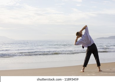 Barefoot businessman doing exercises on a tropical beach